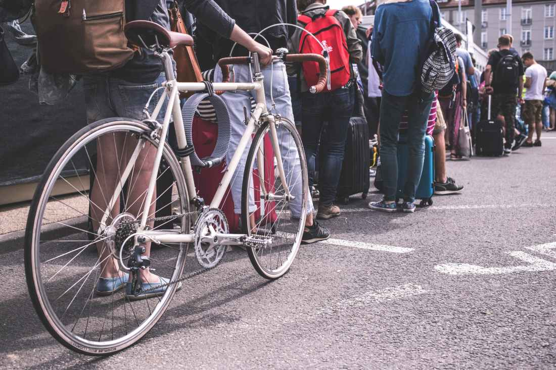 A queue of people, one with a bike - 23 Things You Should Know Before Visiting The UK