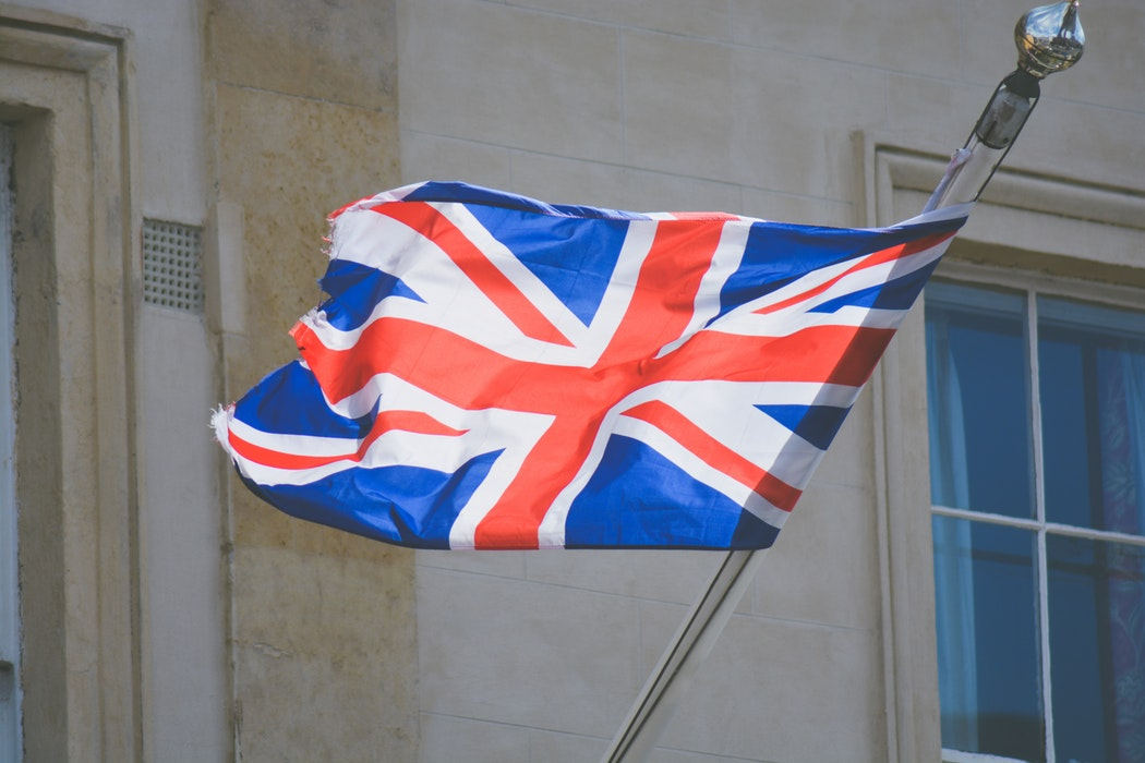 A British flag flies from a flagpole - 23 Things You Should Know Before Visiting The UK