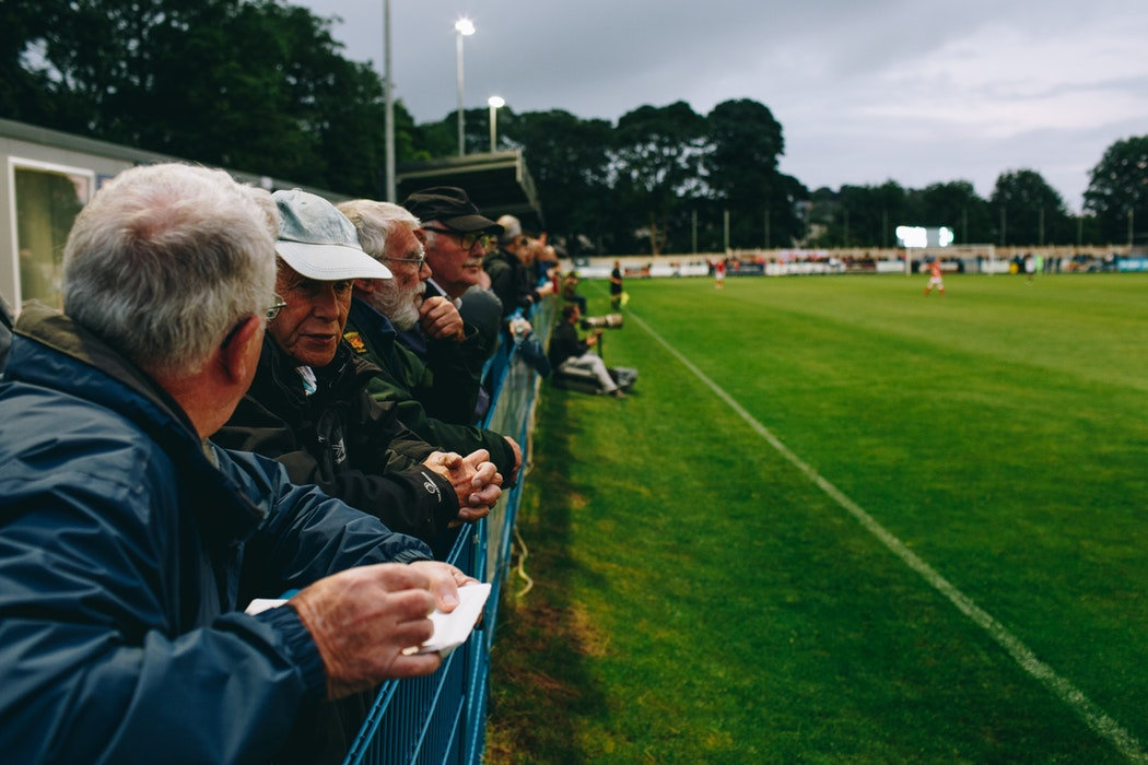 A line of men watch a football match - 23 Things You Should Know Before Visiting The UK