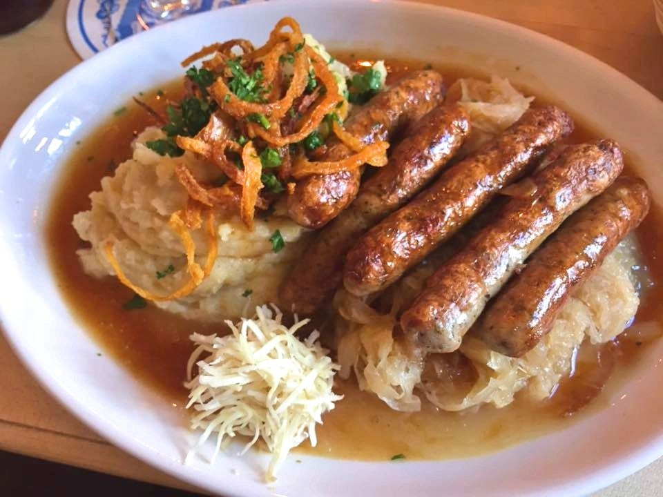 A plate of five sausages perched on a bed of sauerkraut. This cabbage dish is definitely a traditional German food.