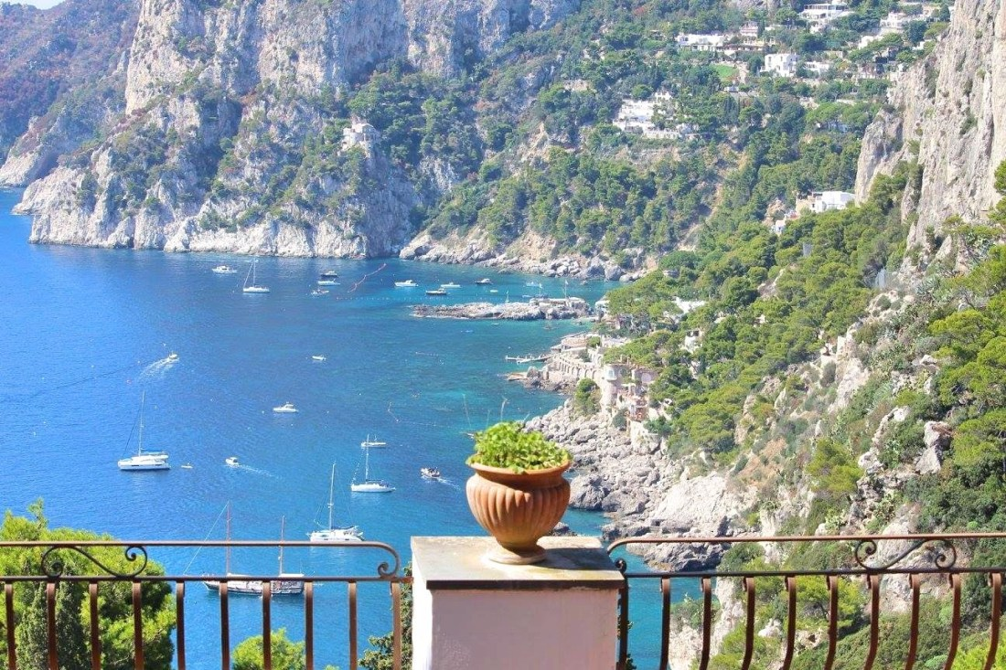 View of blue sea in Capri, with a floral urn in the foreground