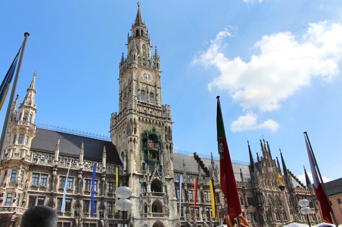 The Marienplatz in Munich, a building with a high tower, and many flags outside. Best known for Oktoberfest, Munich is actually one of the best city breaks in Europe.