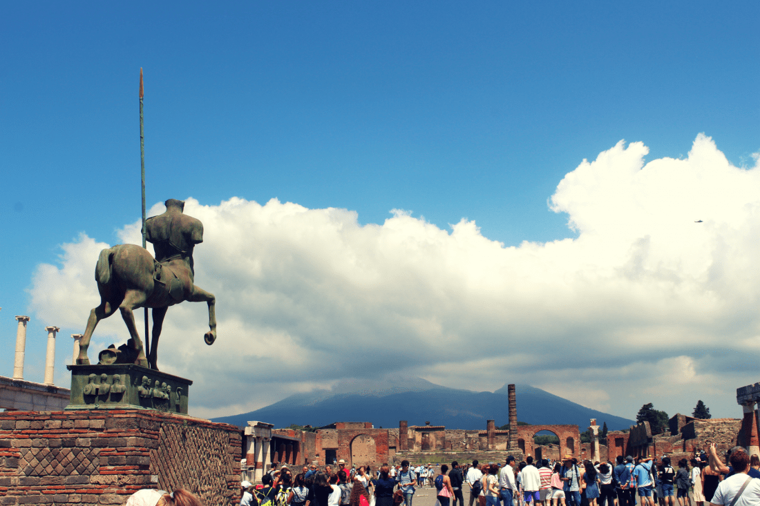 A statue in Pompeii faces towards the bulk of Vesuvius in the distance. Italy is a perfect destination for slow travel!