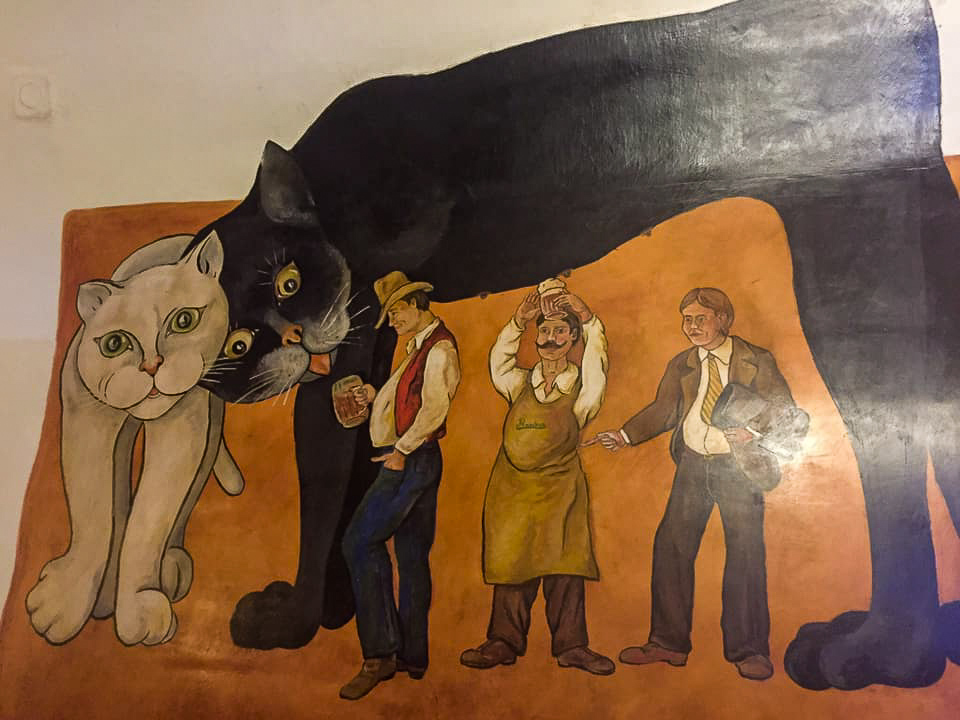 Mural showing man milking beer from a cat, Prague