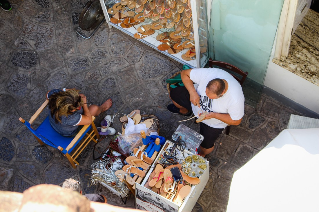 Man makes sandals while a customer watches