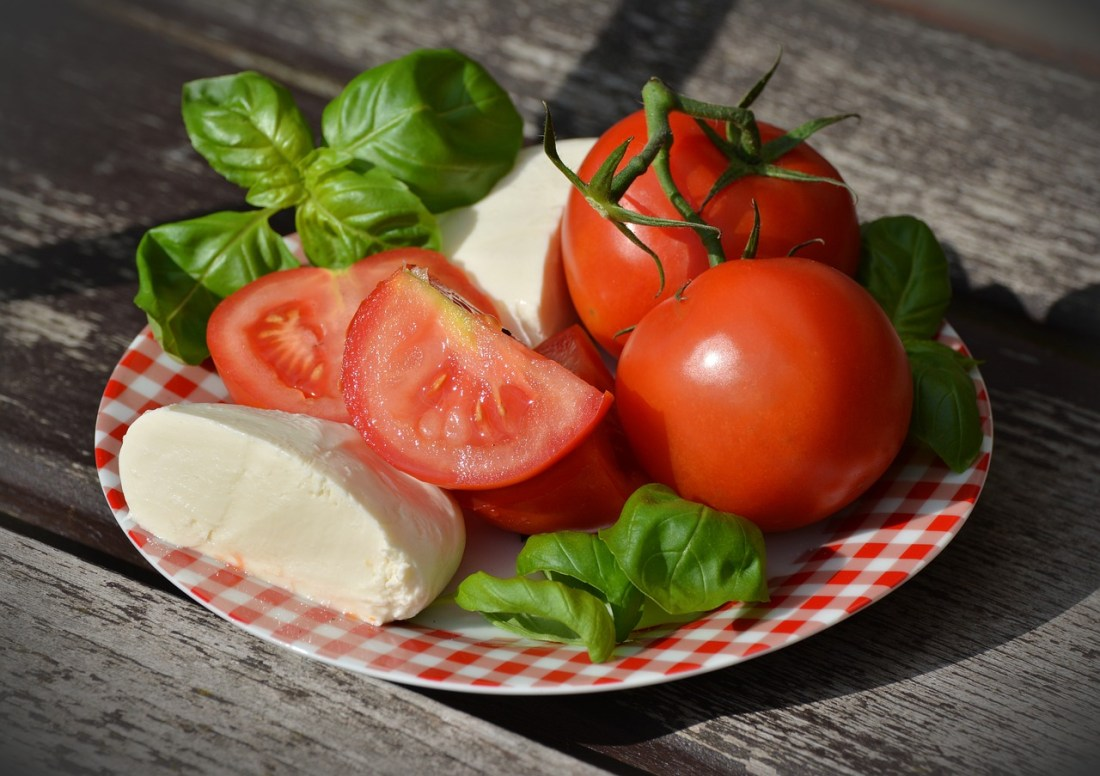 A plate of fresh tomatoes, basil and mozzarella