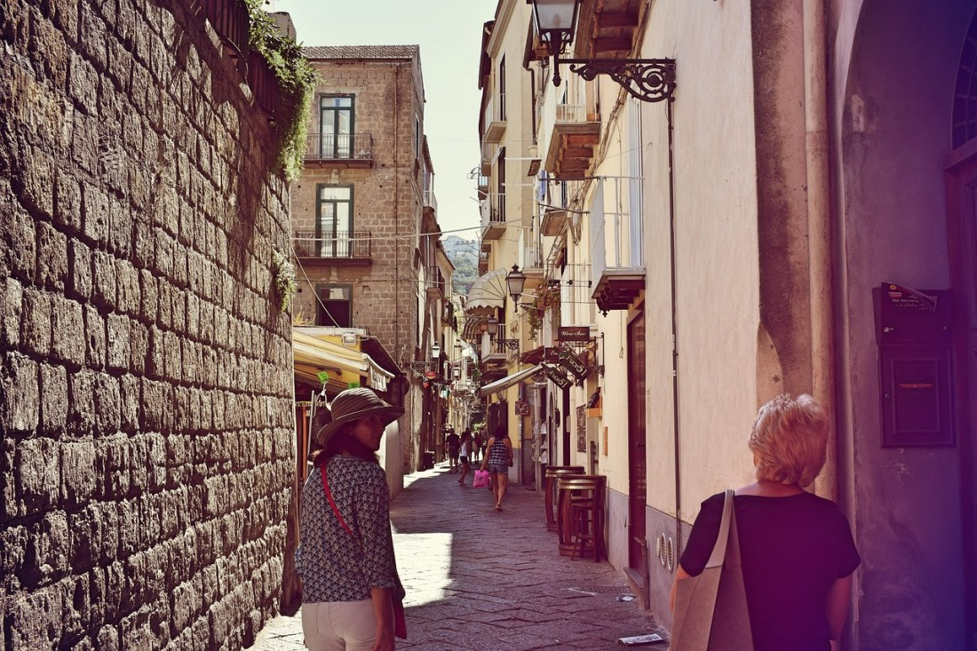 A woman wearing a hat walks through the streets of Sorrento