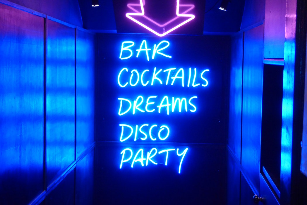 "A neon sign reads ""Bar, Cocktails, Dreams, Disco, Party"""