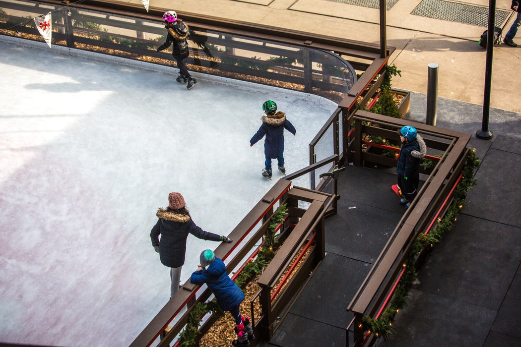 Three children skating on an ice rink