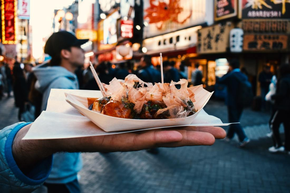 A man holds a tray of street food dumplings in Japan