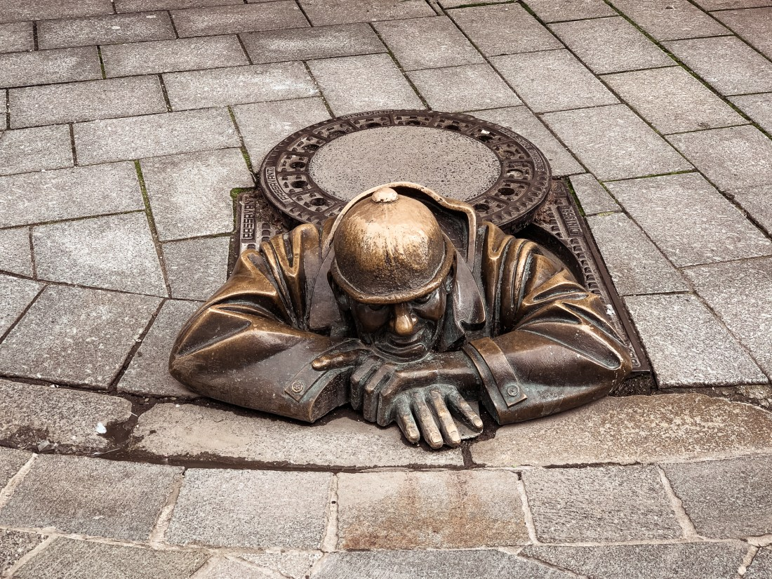 A statue in Bratislava of a man looking out of a manhole
