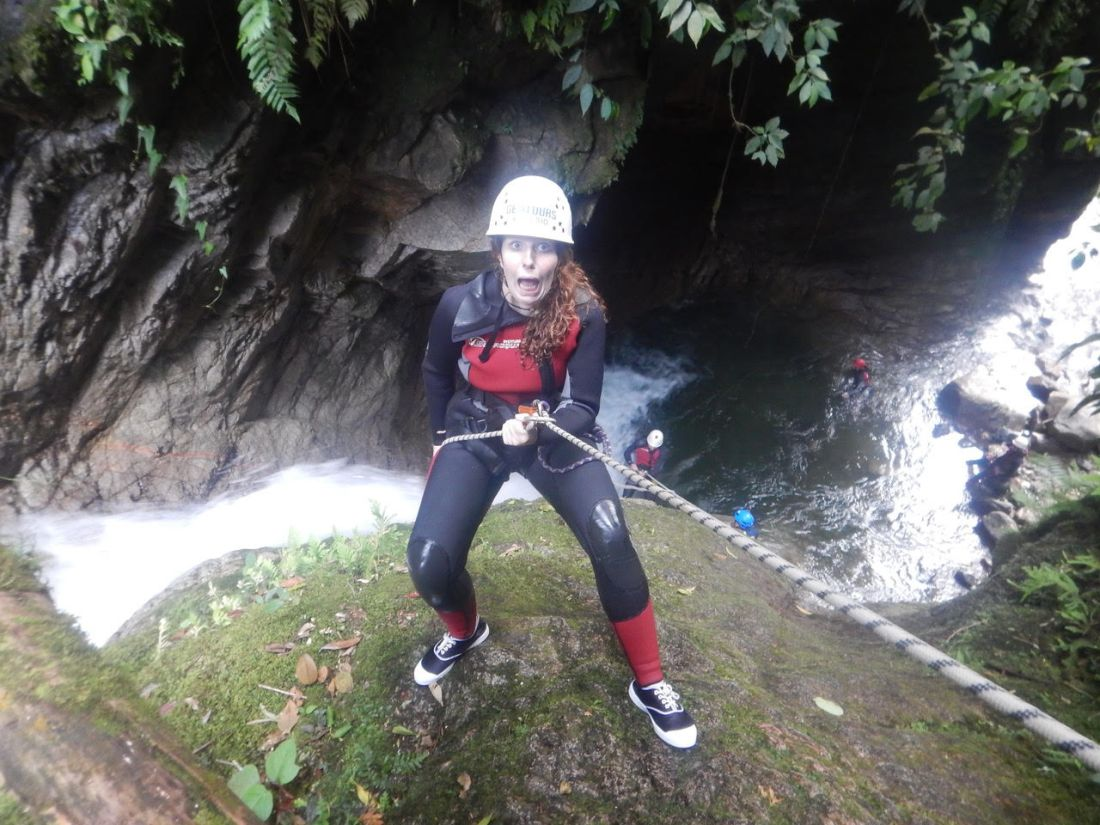 A young woman looks scared whilst canyoning - How to Overcome Travel Anxiety - Travel Bloggers' Stories