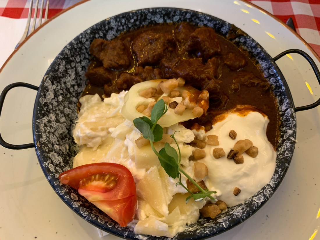 A bowl of Hungarian beef stew, in a bowl with cottage cheese pasta