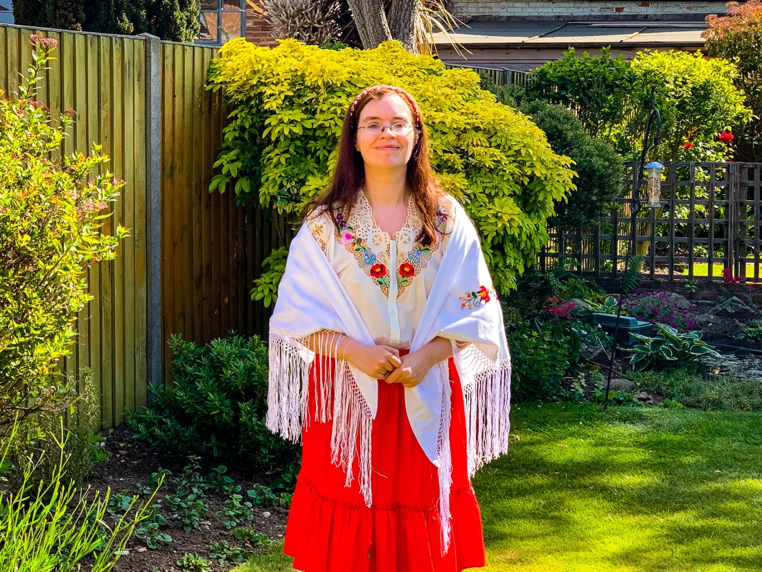 A woman in a traditional Hungarian costume, comprising of a red skirt and white shawl