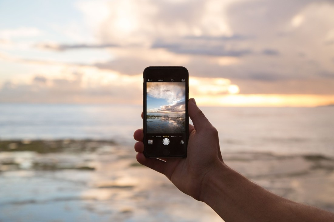 Instagram Travel. A person takes a photo of a seaside on their mobile phone