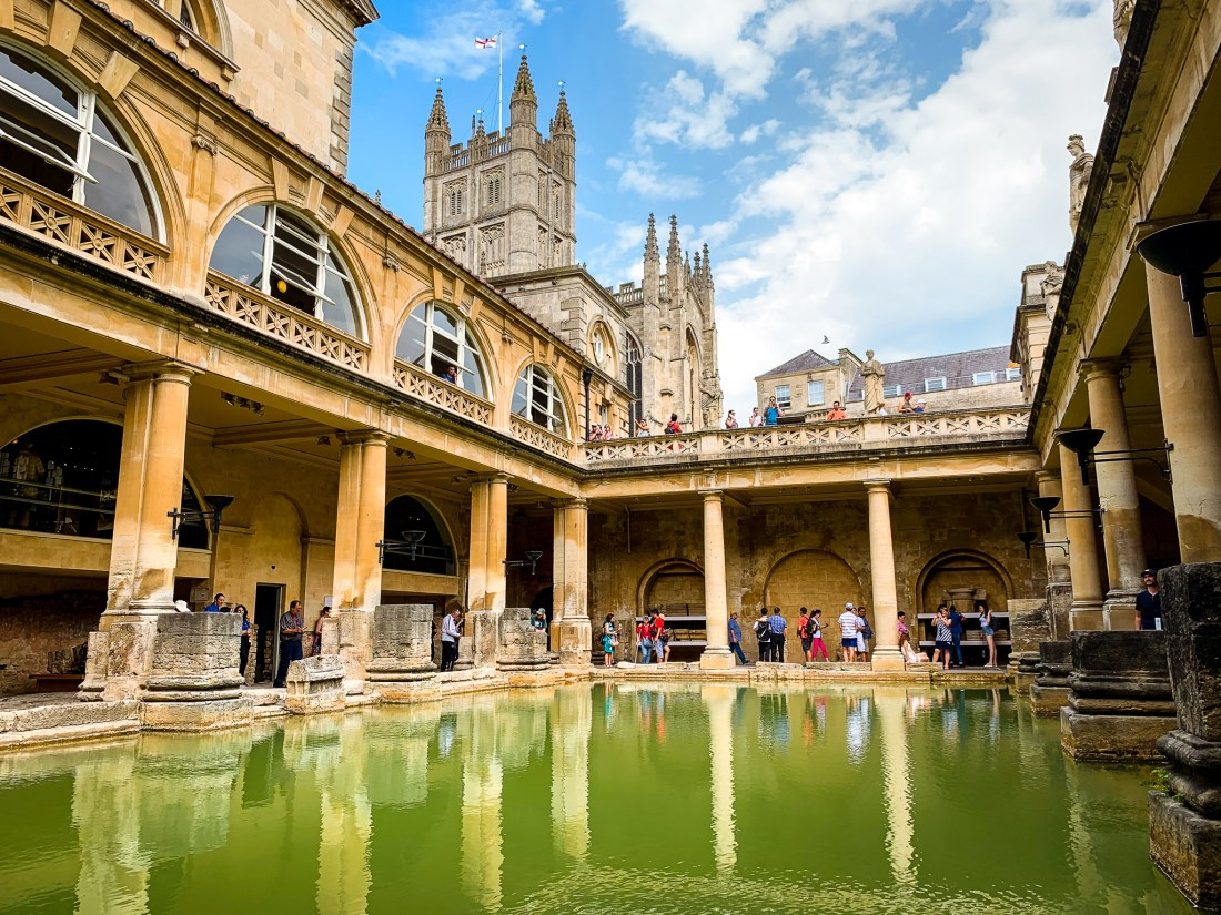 The Roman Baths at Bath, one of the best day trips from London, with green water, and Bath Abbey visible in the background