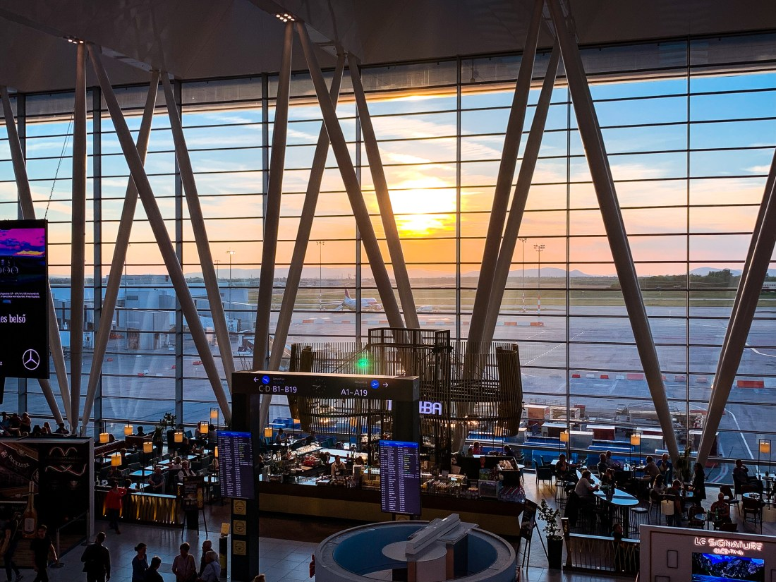 A sunset is visible through the windows of Budapest Airport, the most common way of how to get to Budapest