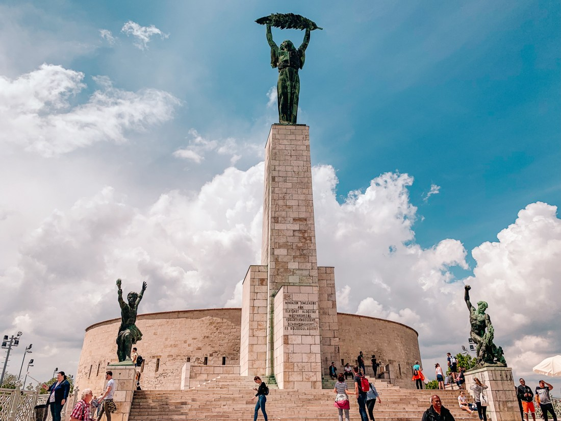 The Liberty Statue on top of Gellert Hill in Budapest. A metal woman stands on top of a large pillar, holding a palm leaf aloft.