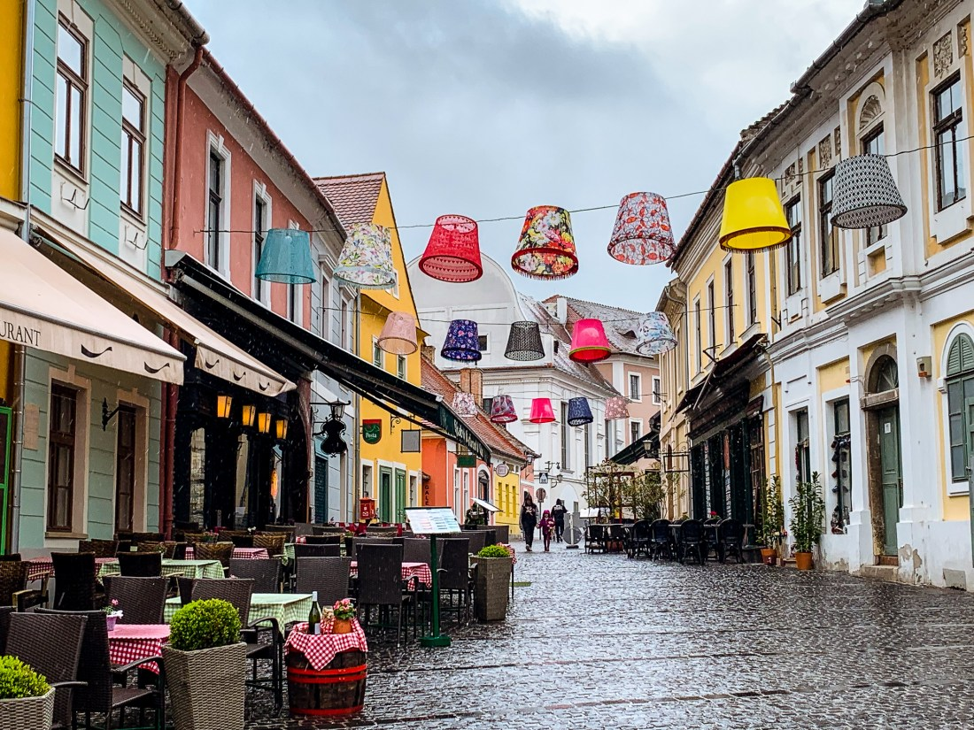The pretty village of Szentendre - lampshades are strung above an old town street, with colourful houses on the side.