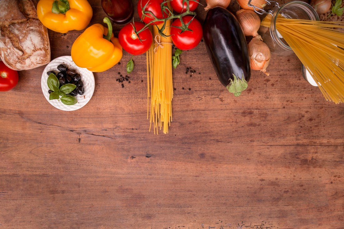 Italian vegetables and pasta on a wooden table. Quotes about Italian food generally capture the simple, yet tasty, nature of Italian cuisine.