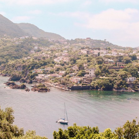 The view from Castelo Aragonese in Ischia. A sailboat sails down a narrow channel between the castle and the land.