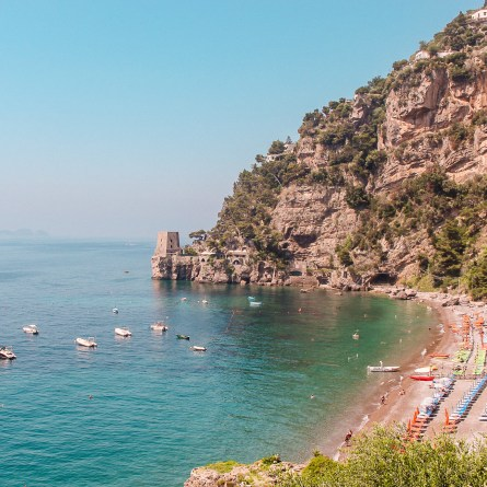 A view of Fornillo Beach, with blue seas and tiny boats on the sand.