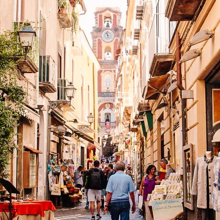 People shopping on a street in Sorrento with a church tower in the background. Sorrento is one of the most instagrammable spots on the Amalfi Coast