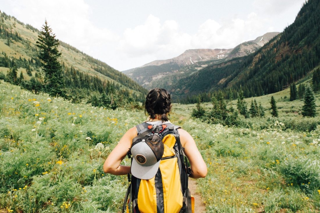 A woman stands in a field with a black and yellow backpack. Buying a trip for someone is the most expensive of travel gifts, but most appreciated.
