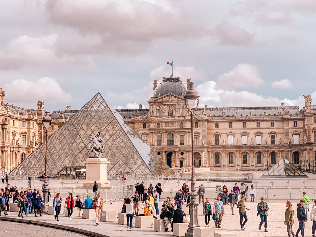 The Louvre Museum in Paris, with the famous glass pyramid outside. A group of people are walking past and taking photographs.