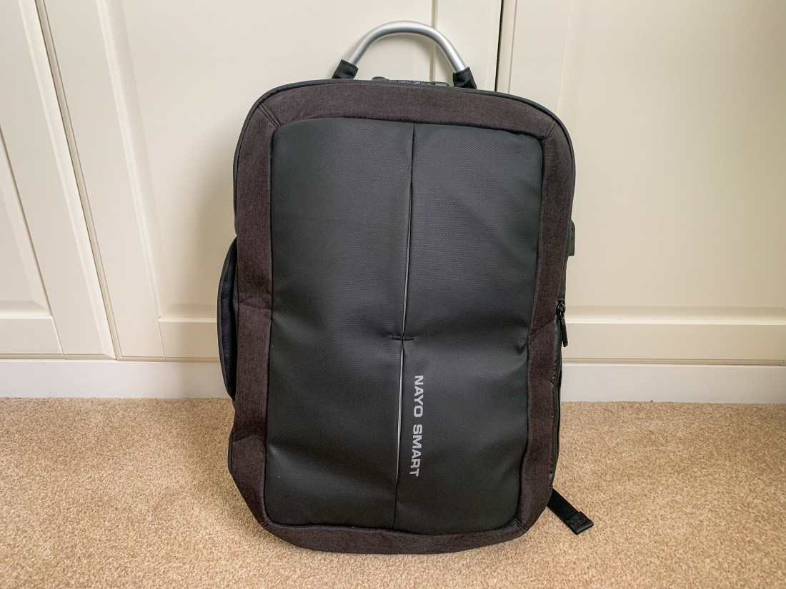 The front view of the Nayosmart anti theft backpack - a black rectangular shape with metal handle.