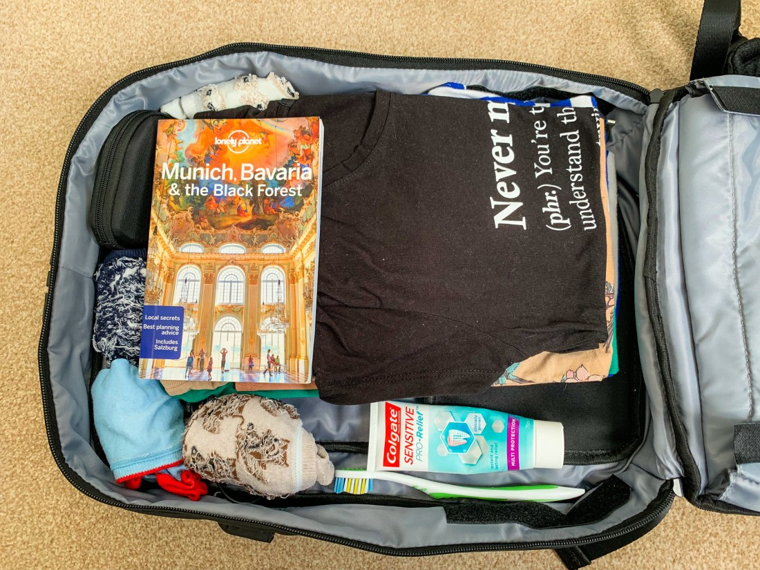 A packed backpack, containing t-shirts, socks, books, and toothbrush.