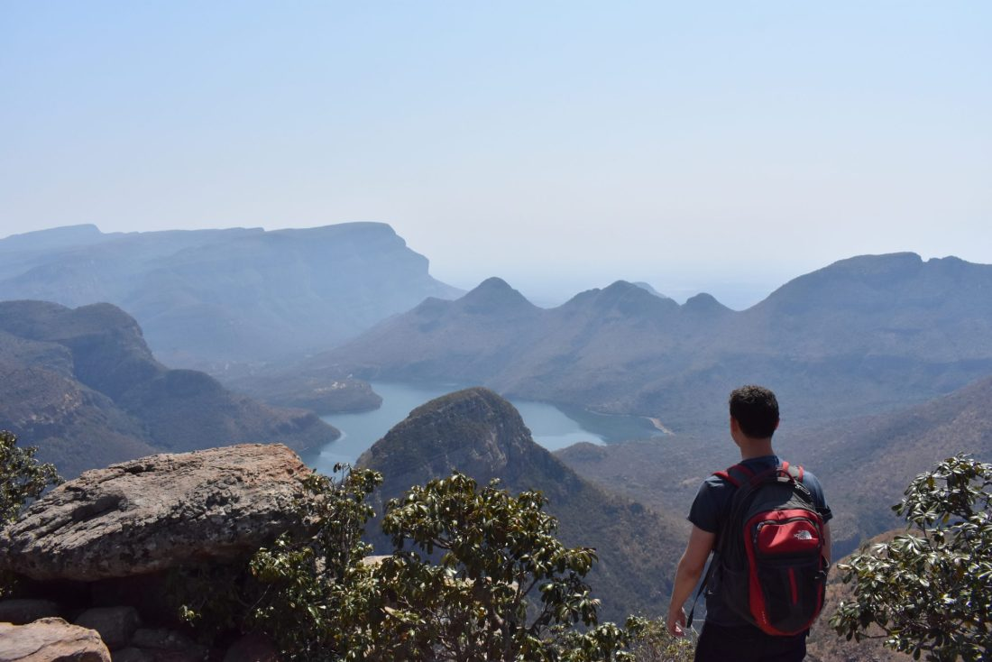 Matt Kepnes stands on an clifftop overlooking a gorge and lake in Africa