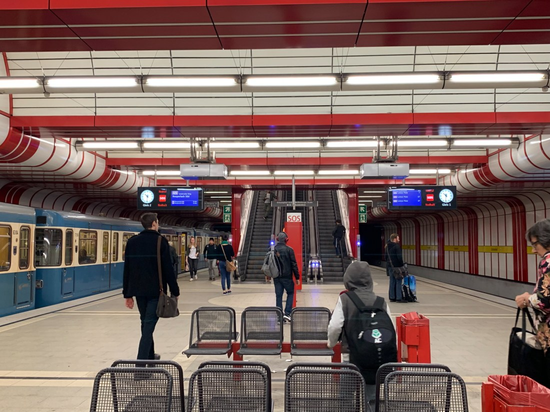 An underground station in Munich with commuters walking along the platform. This is a common scene on Munich public transport.