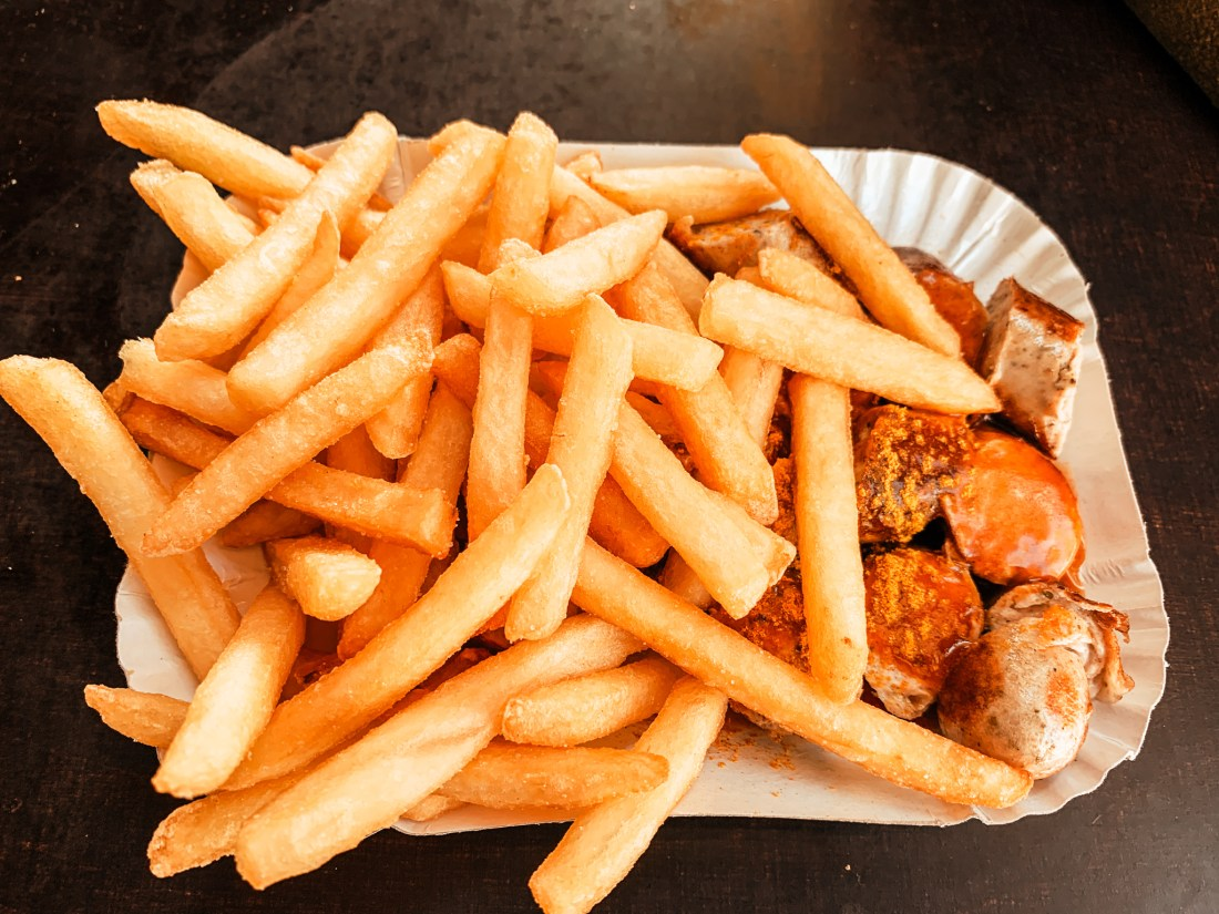 A cardboard plate of currywurst. This is made from chopped sausage, curry powder, and a large amount of french fries.