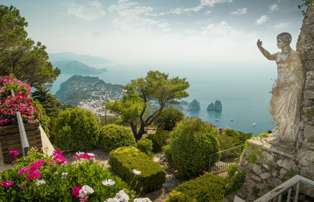 Taking a chairlift up Monte Solaro in Capri is one of the best things to do in Capri guide. A statue and the Faraglioni are visible.