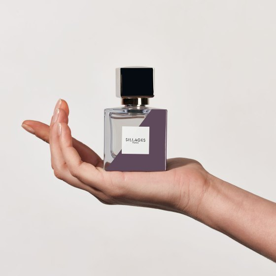 A hand holding a larger bottle of Sillages Paris custom perfume