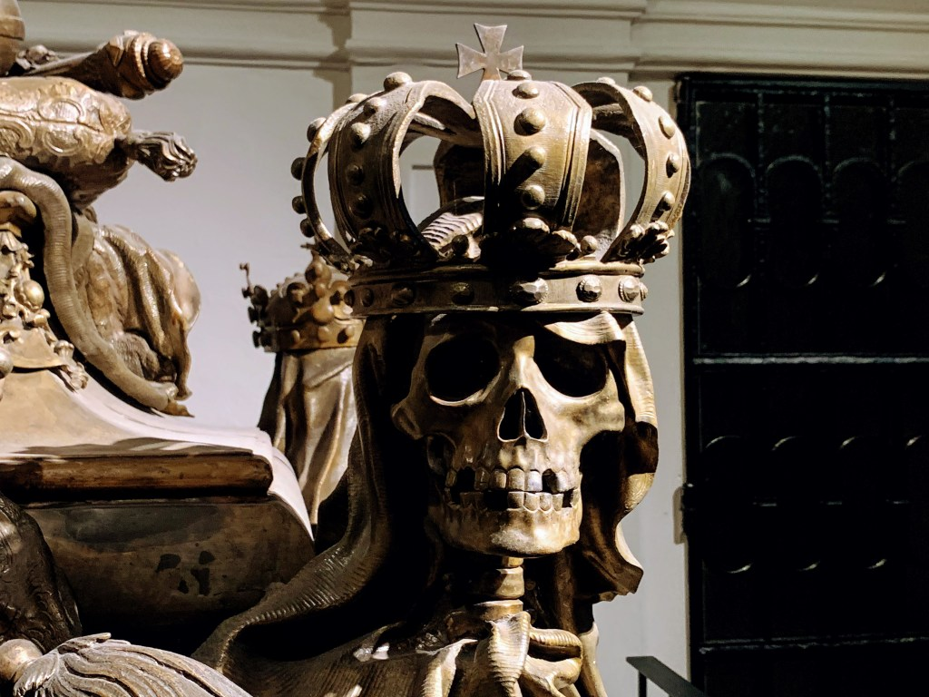 A statue of a skeleton wearing a crown in the Imperial Crypt, one of the most Instagrammable places in Vienna
