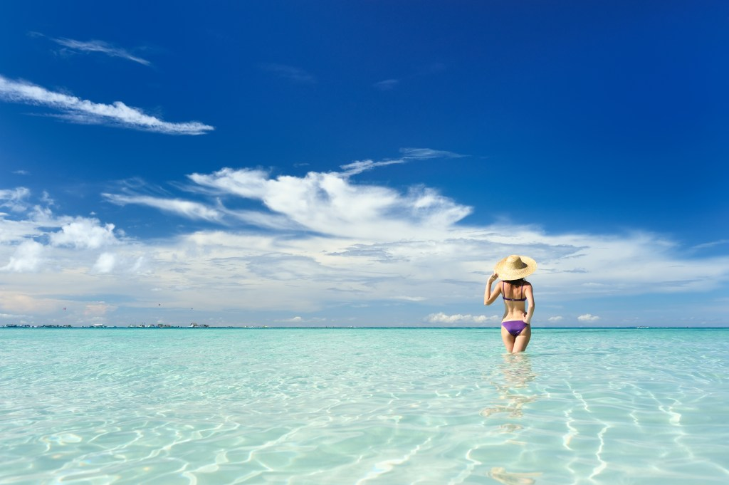 A woman stands in the water on a tropical beach
