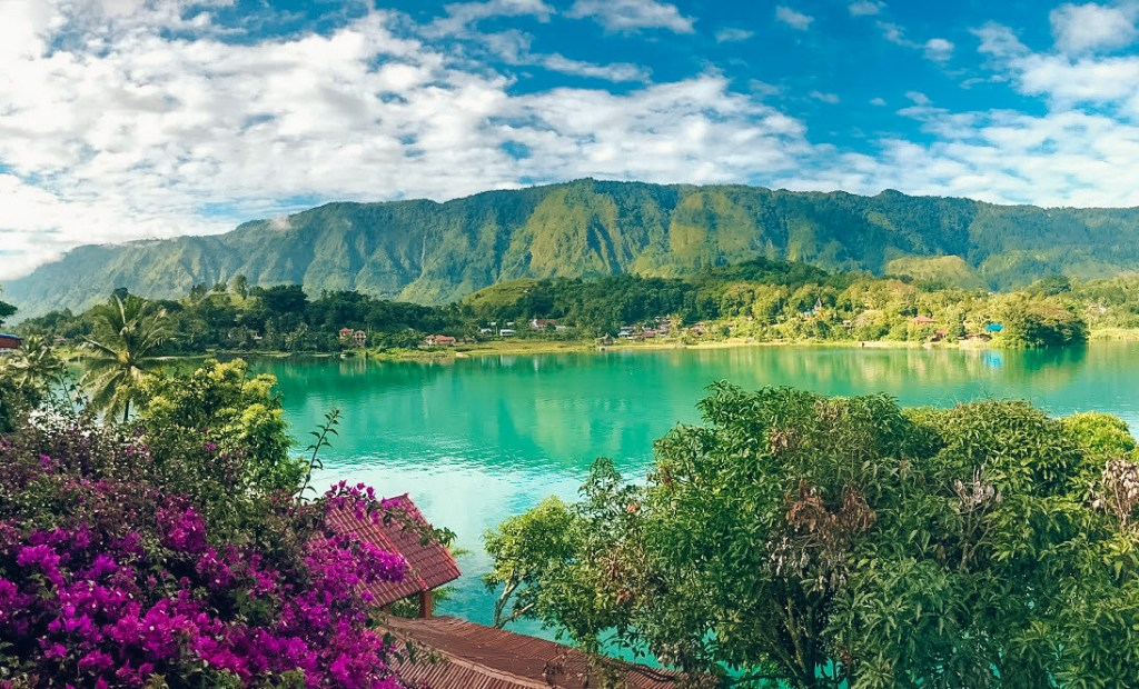 Trees and purple flowers surround Lake Toba in Indonesia