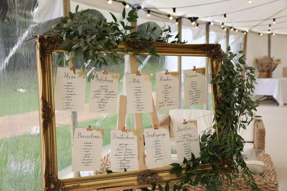 Wedding calligraphy table plan set in ornate gold frame with greenery