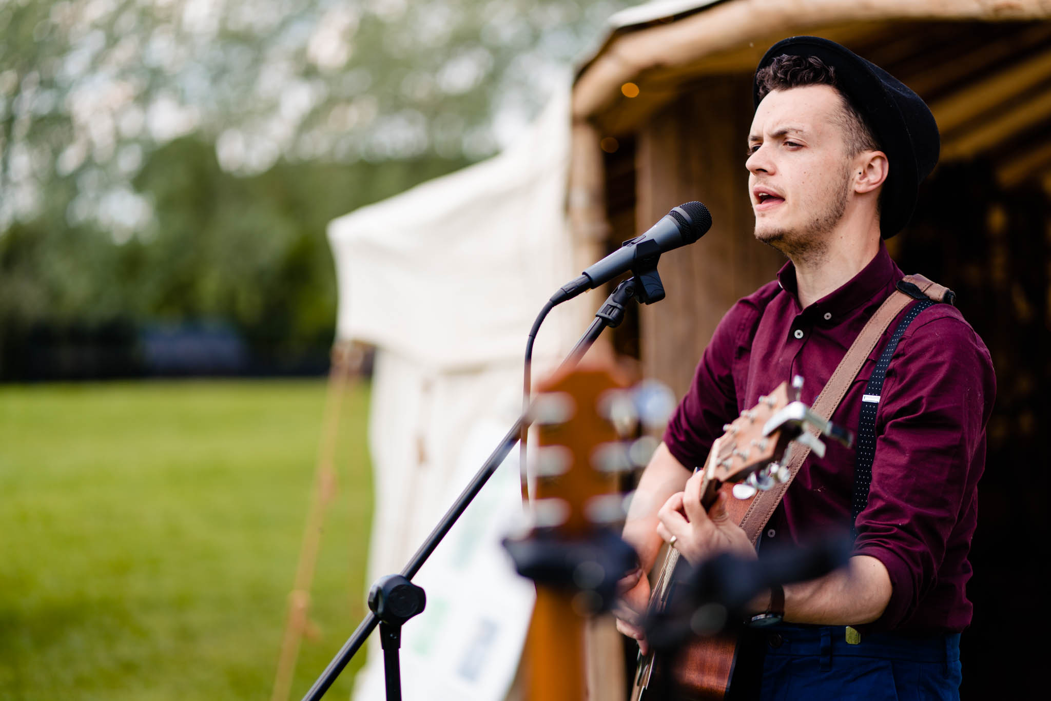 vicki clayson photography - singer captured at festival wedding in front of yurt with his guitar