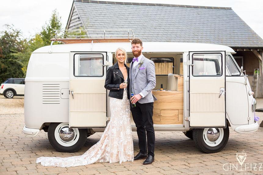 B&N barn wedding day - bride and groom standing outside VW campervan in drinks reception
