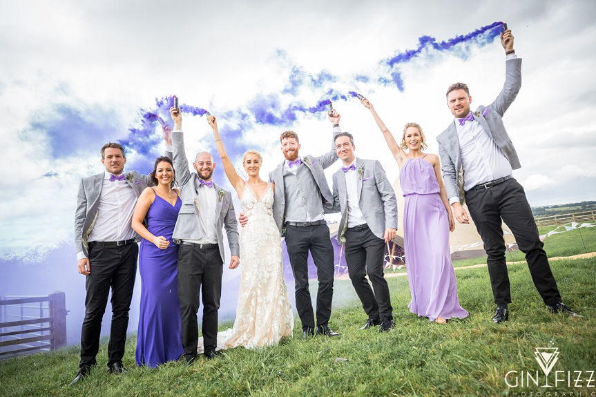 B&N wedding day castle view farm and stables farm leicestershire barn wedding venue - bridal party holding purple smokebombs in front of tipi 2