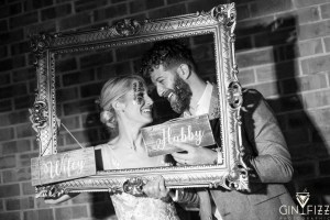 B&N wedding day castle view farm and stables old school photobooth hubby and wifey with large gold frame smiling with glitter
