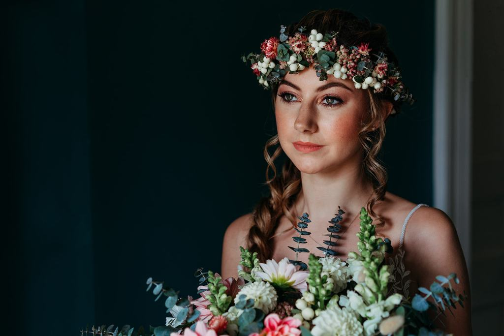 Bride at Fillongley Hall Warwickshire wearing flower crown and holding bouquet in the window