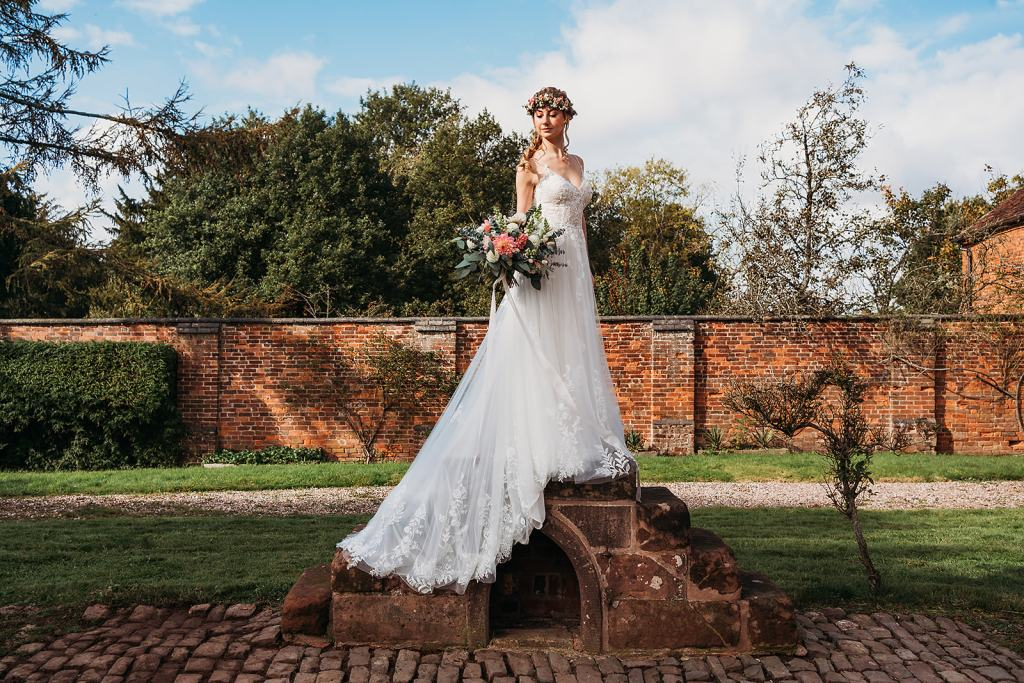 Exclusive wedding venue Fillongley Hall - Grade 2 listed country house with original features - Bride standing on horse mounting block with bouquet