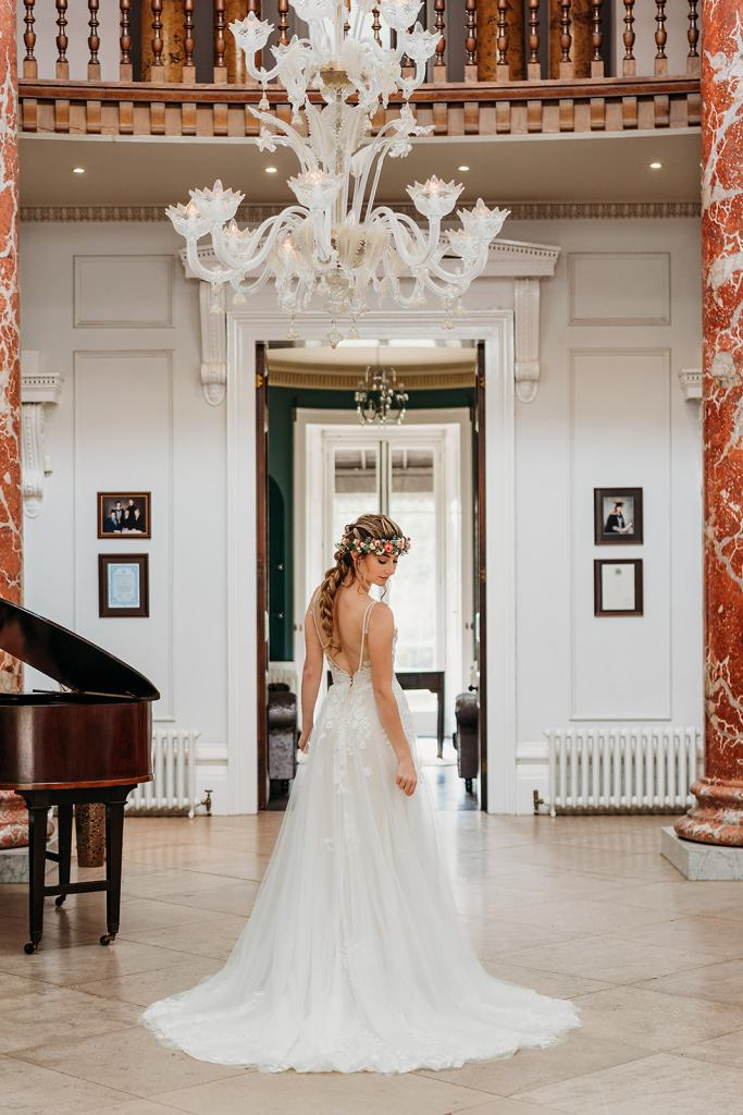 The Entrance Hall at Fillongley Hall with chandelier, balcony and piano. Bride standing in the middle looking at the marble floor.
