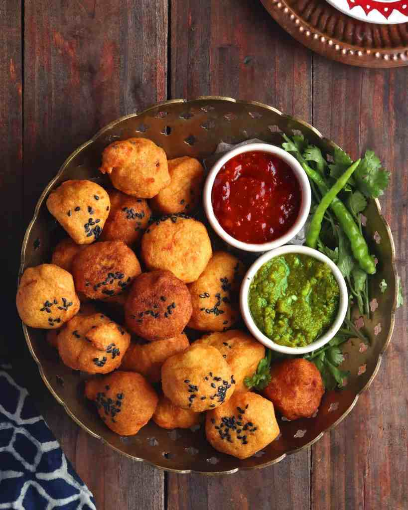 Urad Dal Vada on a copper bowl over a wooden table served with green and red chutney