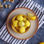 Lemon Truffles in a bowl and white plate on a blue backdrop along will small white flowers