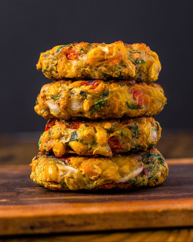 Vegan Corn Fritters stacked on a wooden table